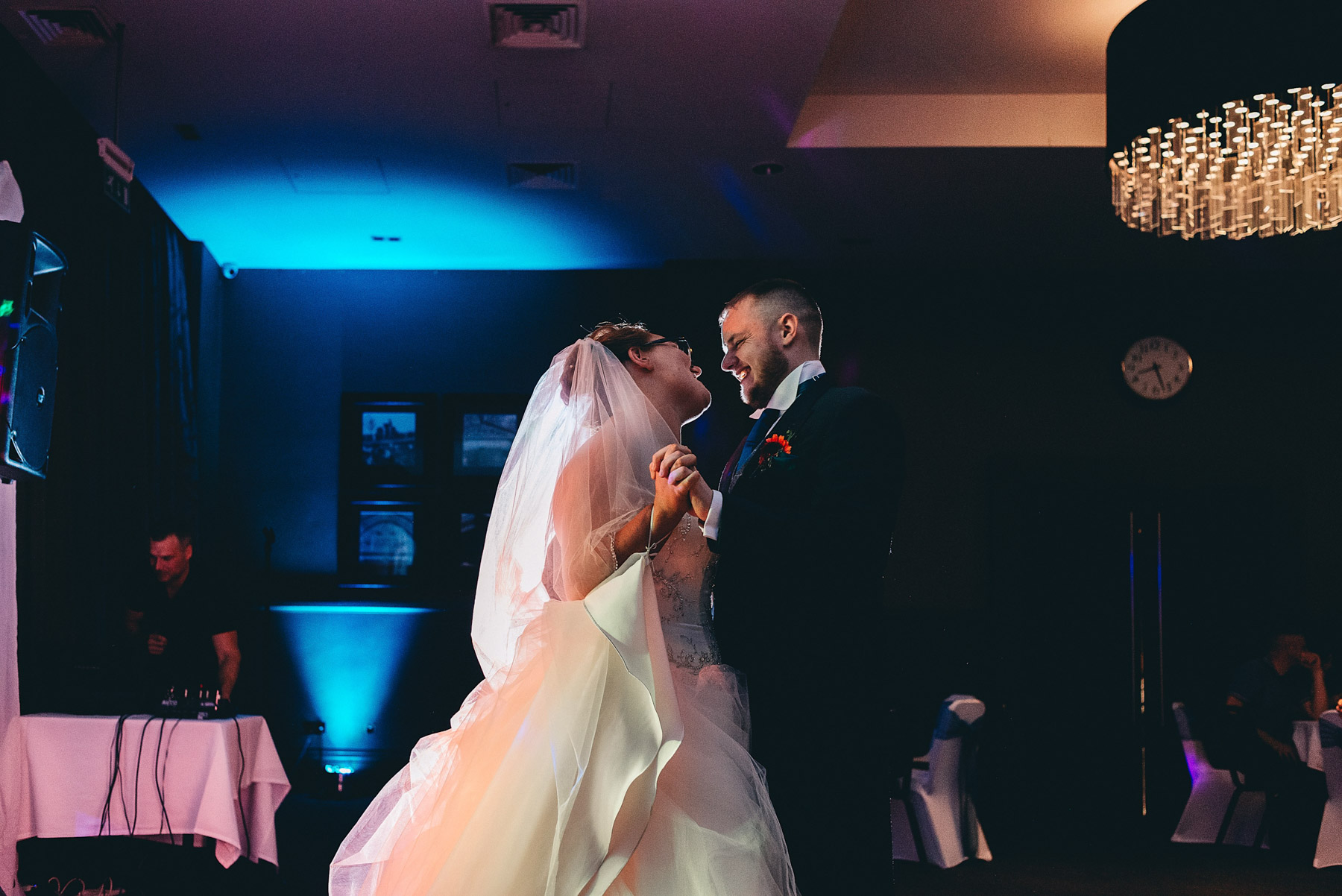 Bride and groom dance with light behind them