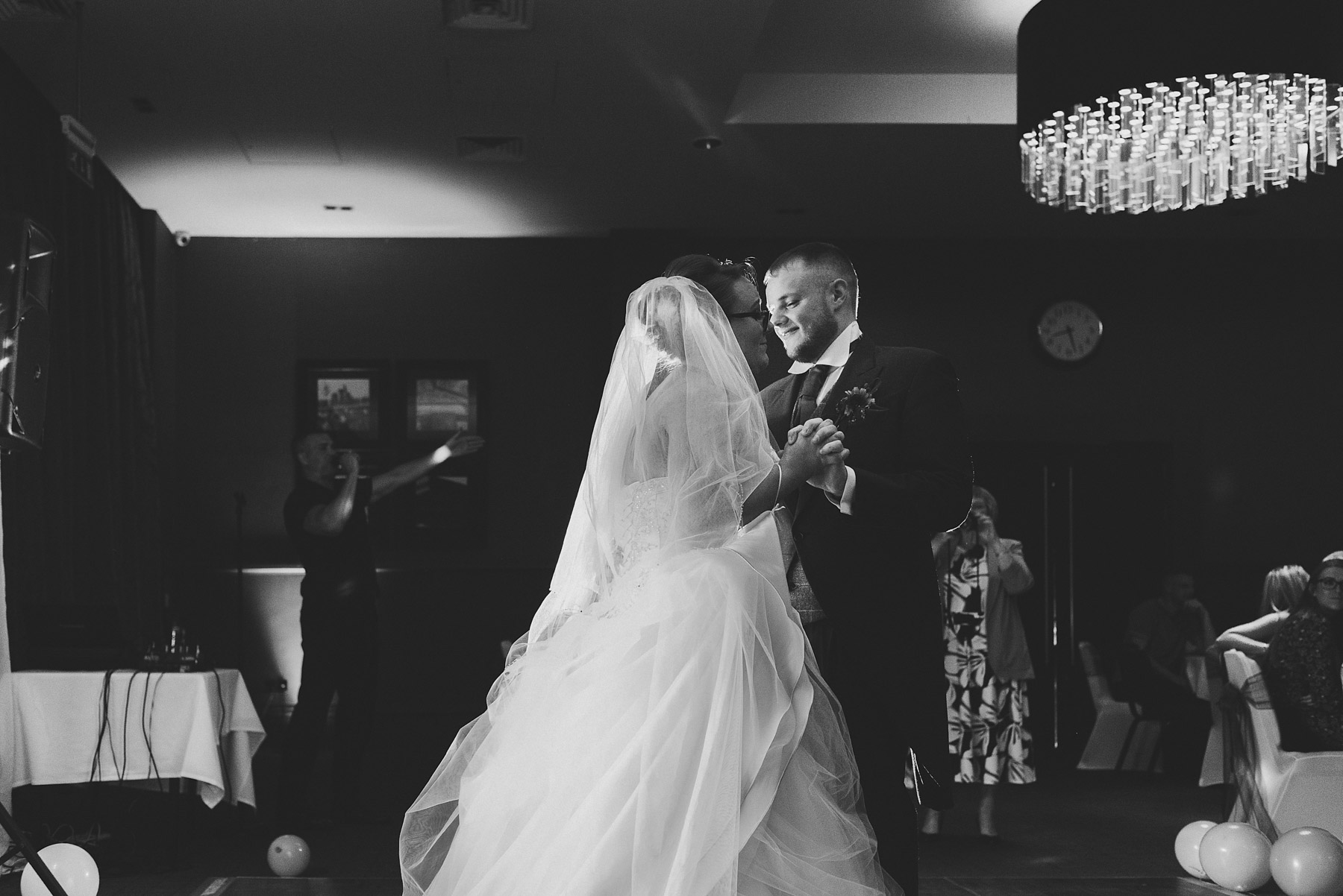 Black and white picture of bride and groom having the first dance
