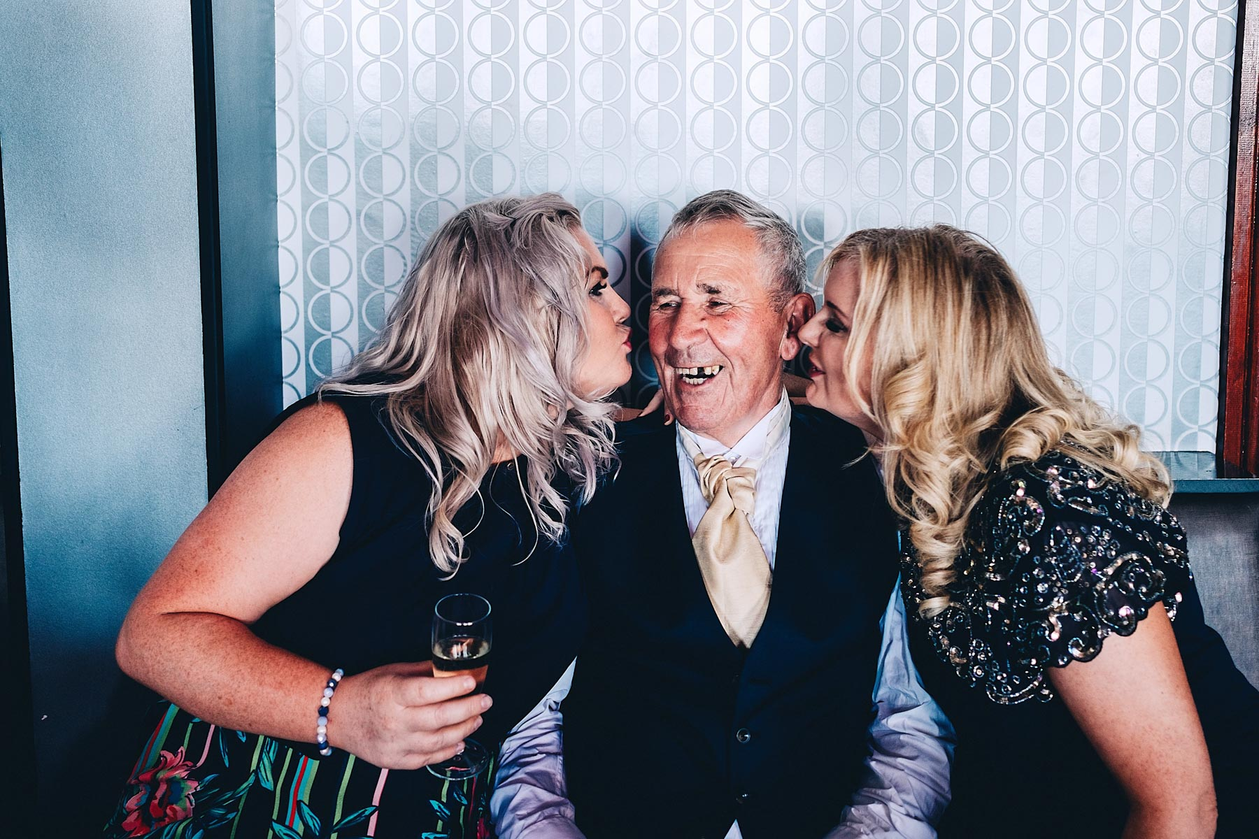 Old man laughs while two younger women kiss him
