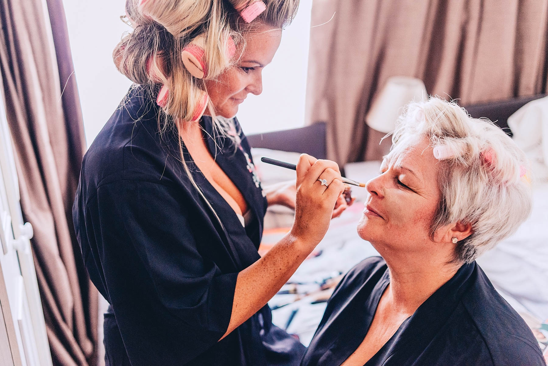 Daughter applying makeup to mother