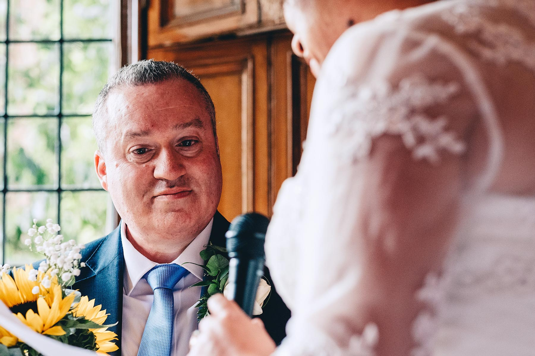 Groom looks lovingly at bride during wedding service
