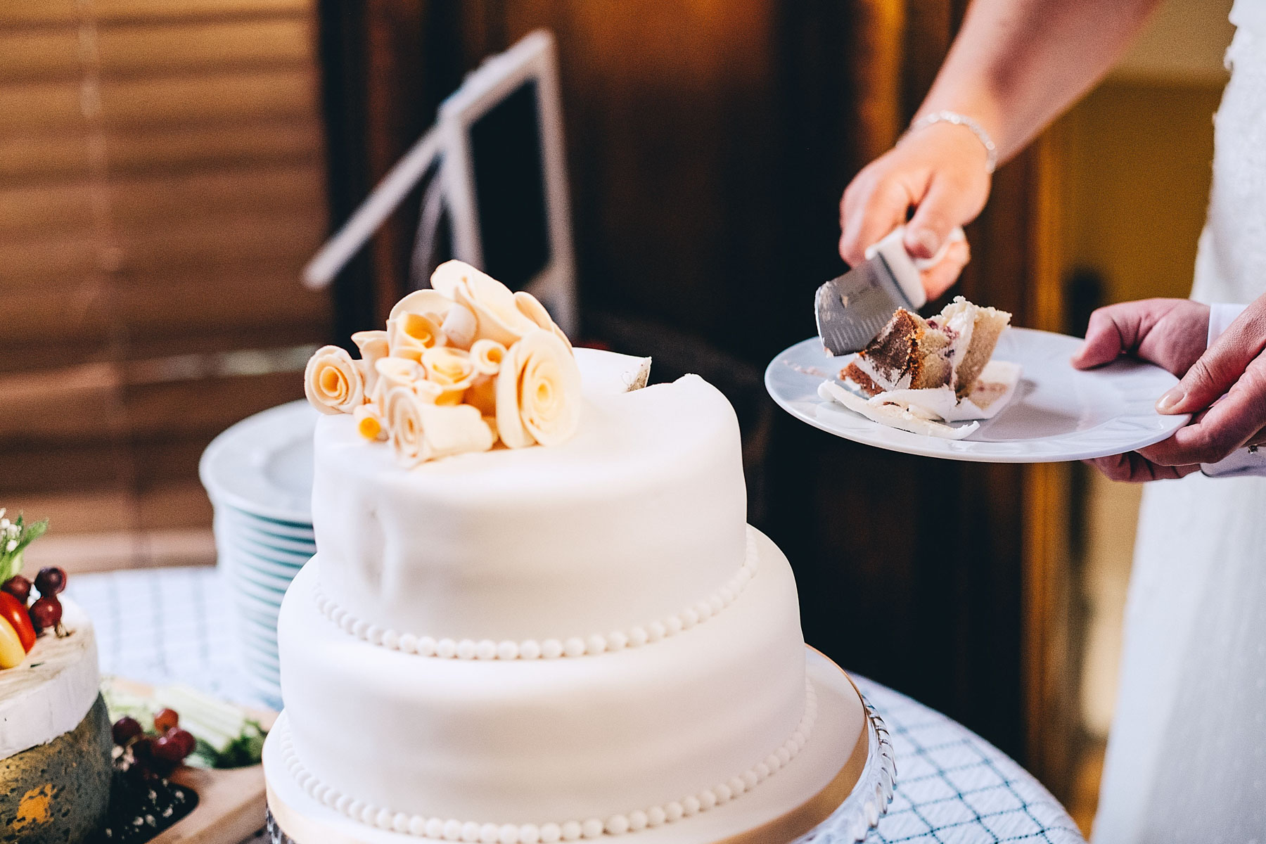 Wedding cake is cut by the bride