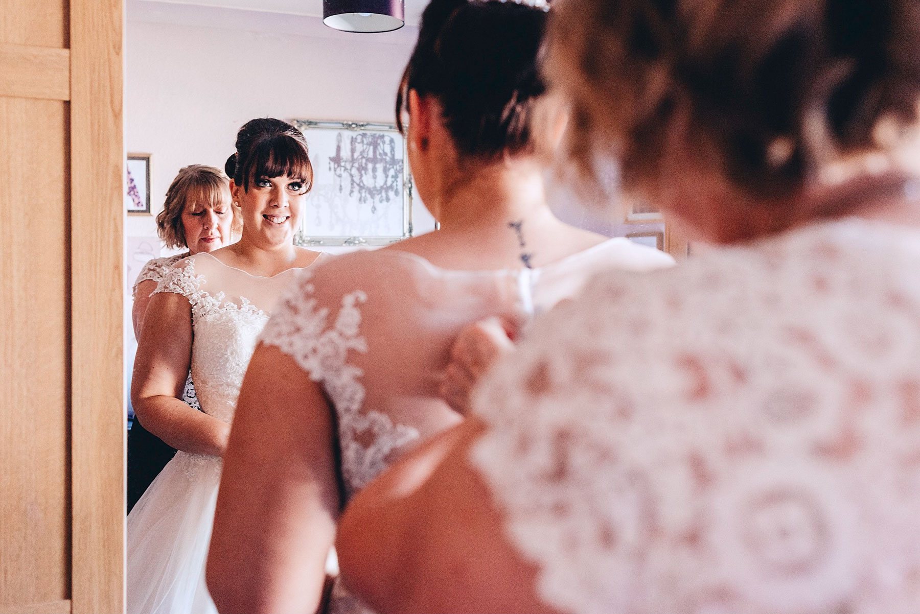 Bride looks in mirror as her mother helps her get ready