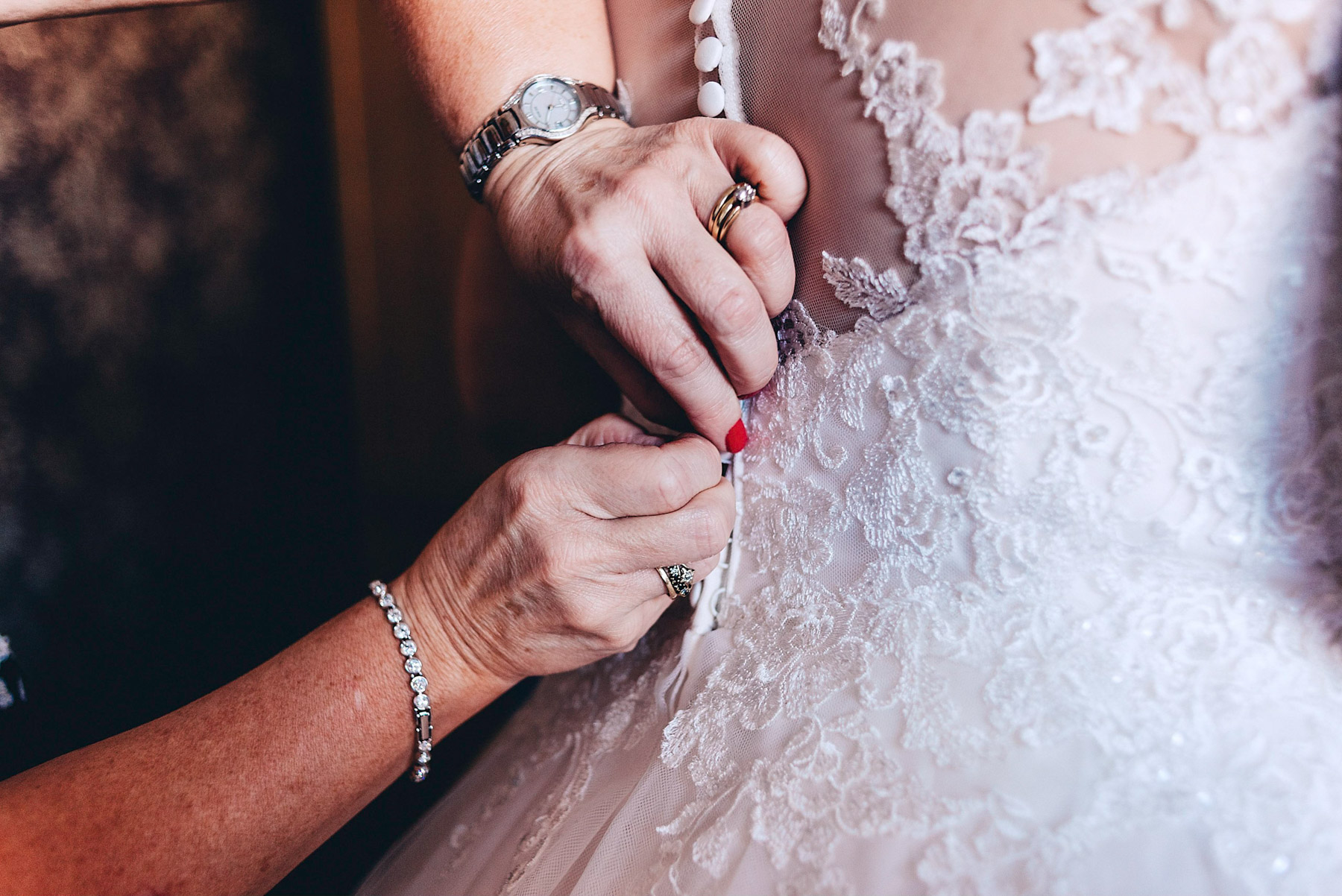 Mother of the bride helps with daughters dress