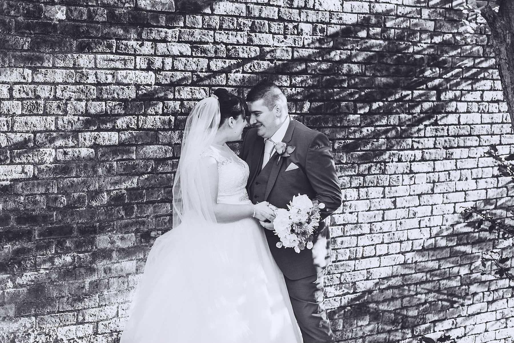 Bride and groom look at each other while light hits a wall behind them
