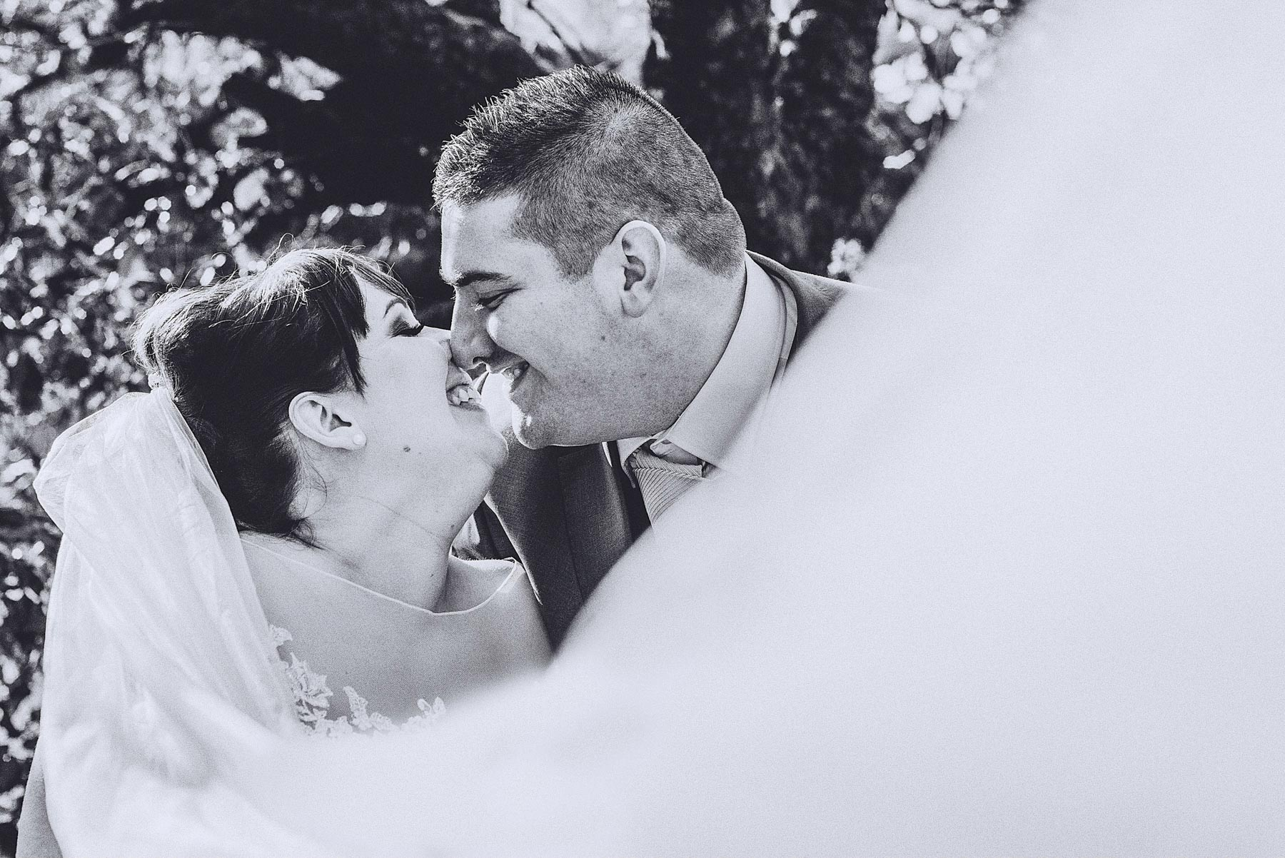 Bride and groom laugh while veil blows across them