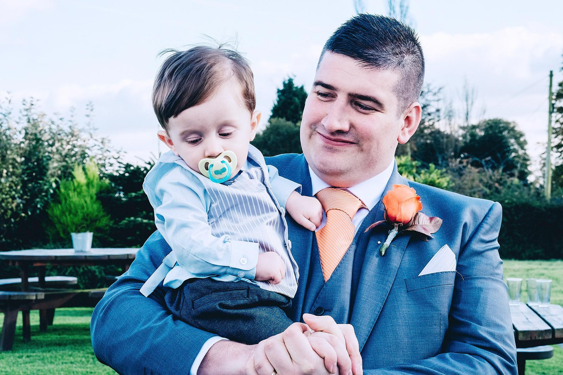 Groom holds son proudly