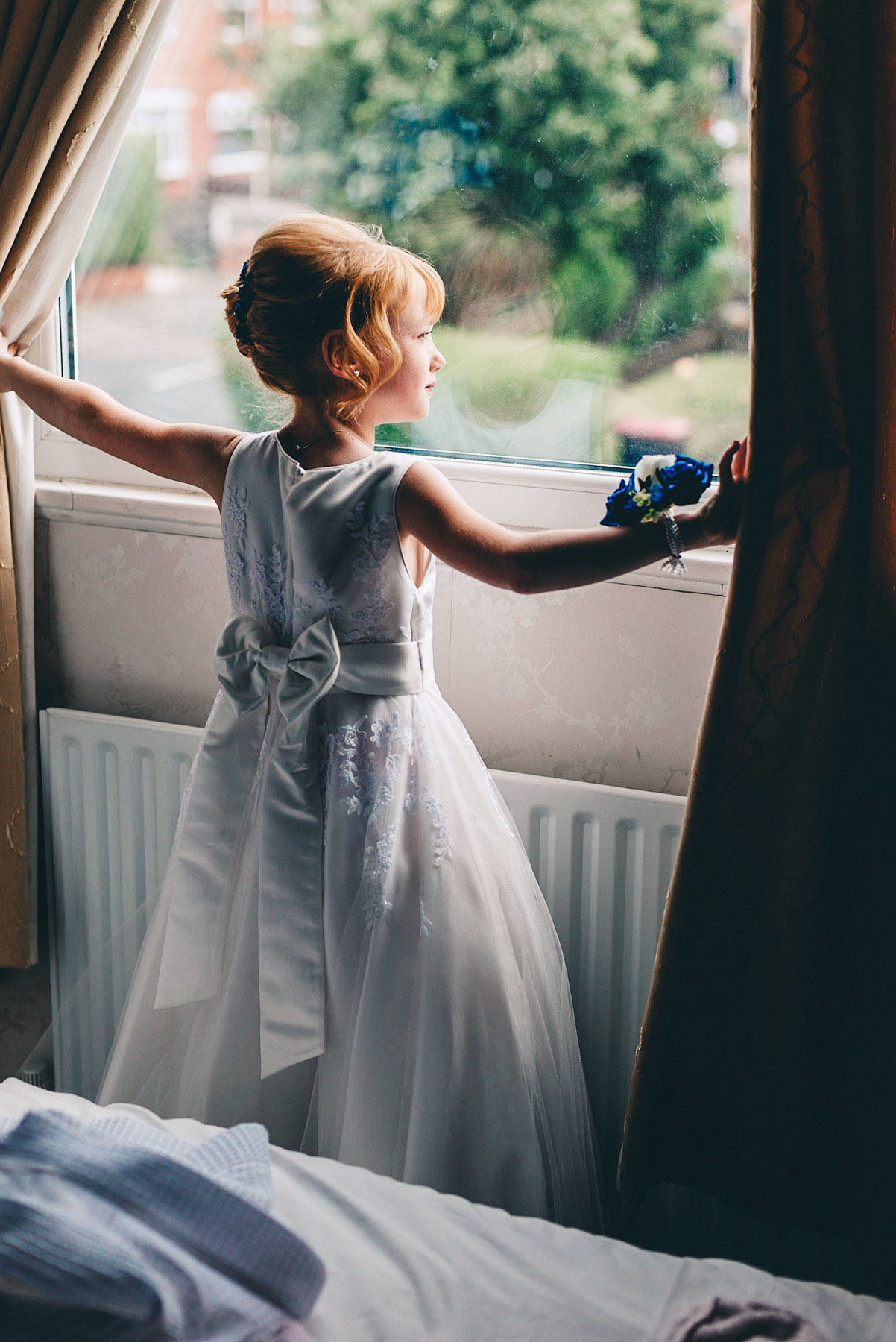 Girl looks out of window on morning of wedding
