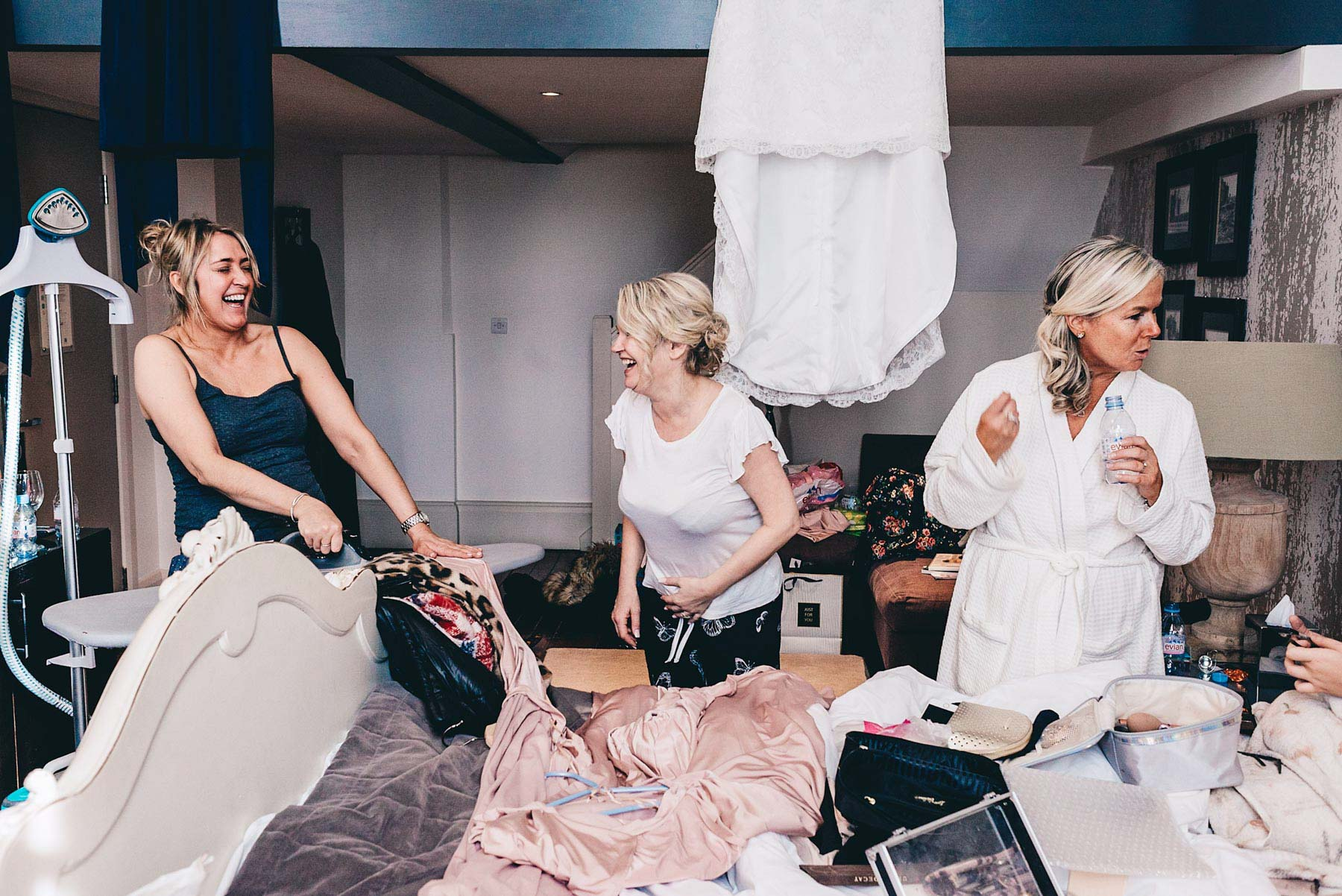 Bridesmaids laugh while ironing, morning of manchester wedding