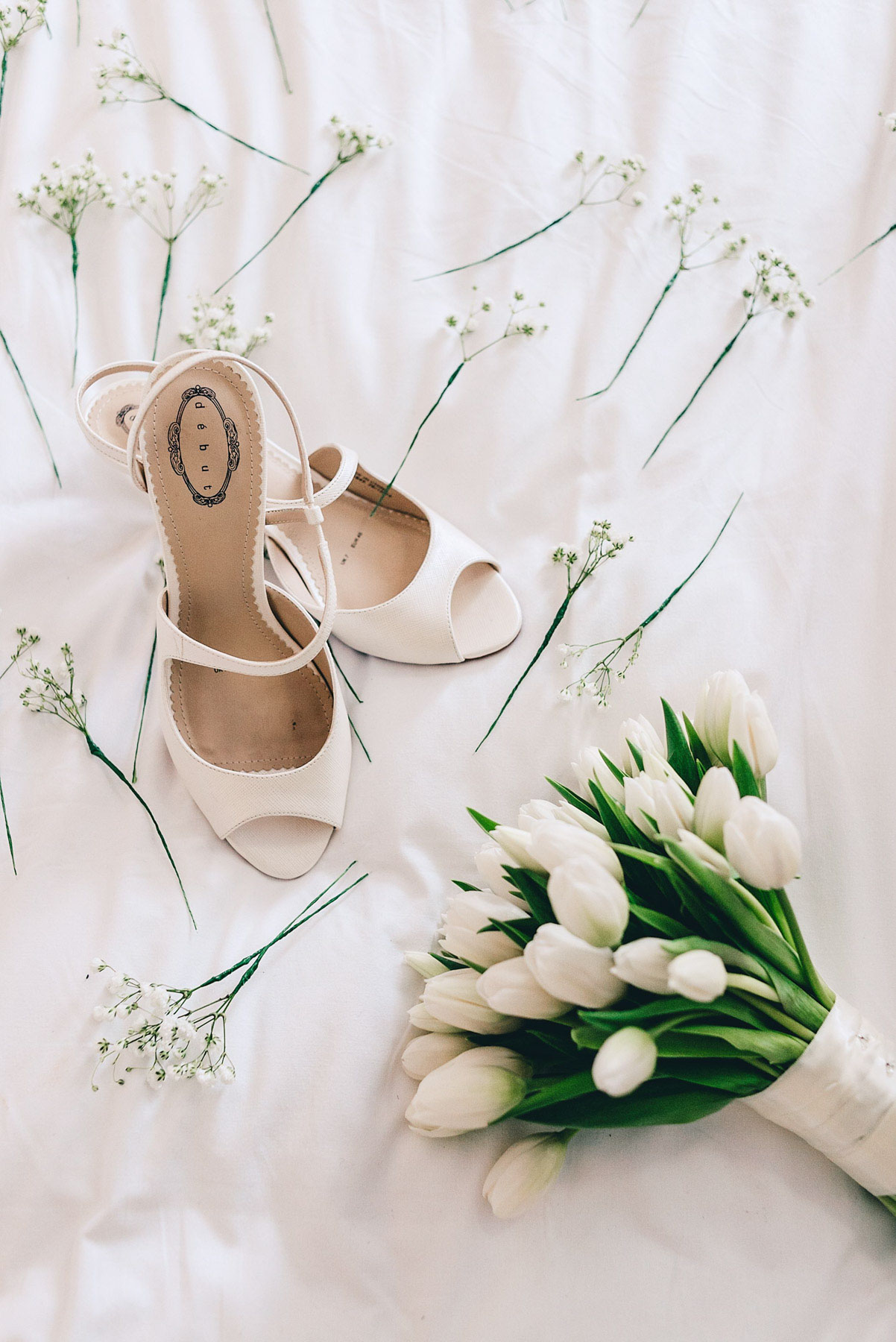 Brides shoes and flowers on bed