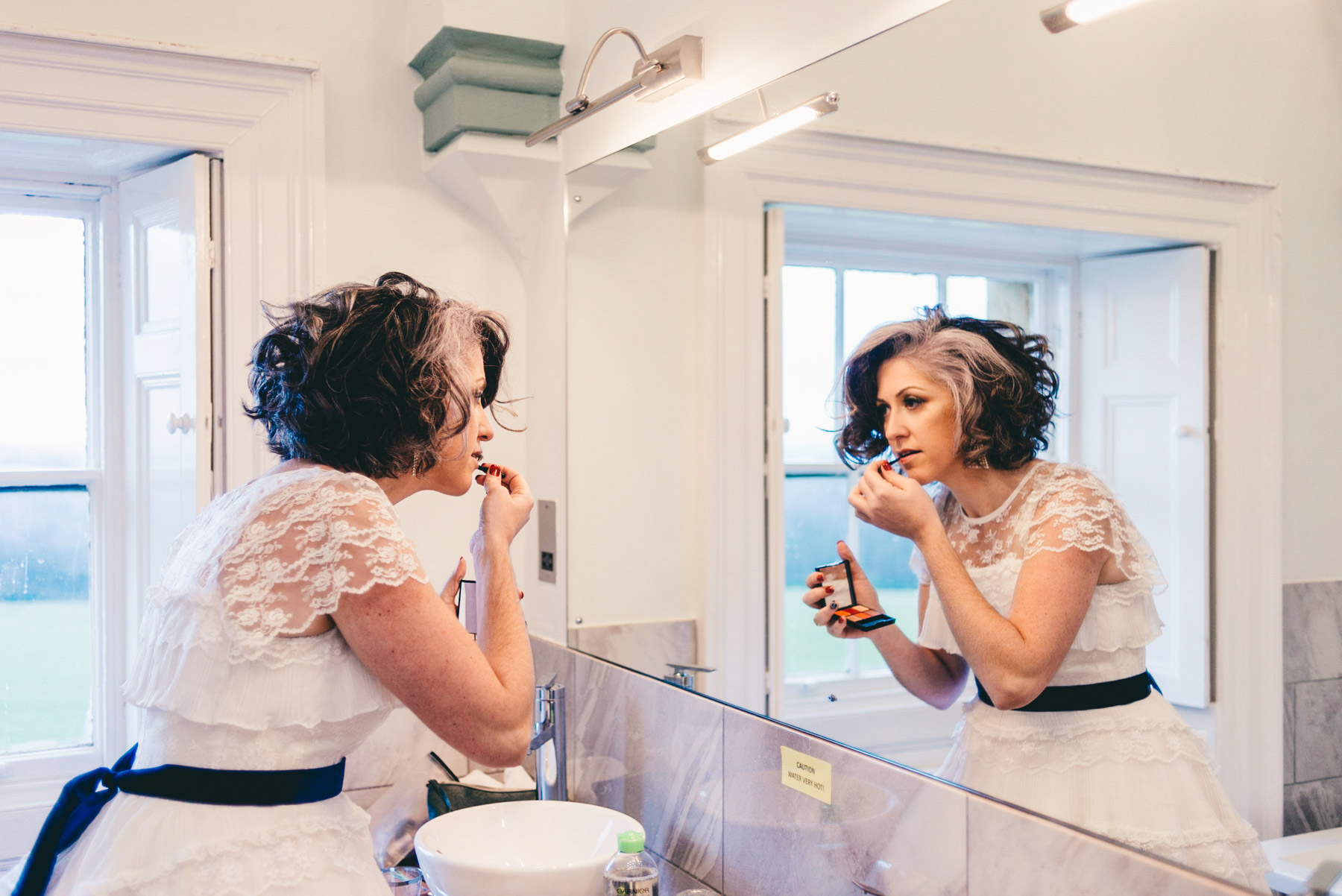 Bride applies own make-up in mirror