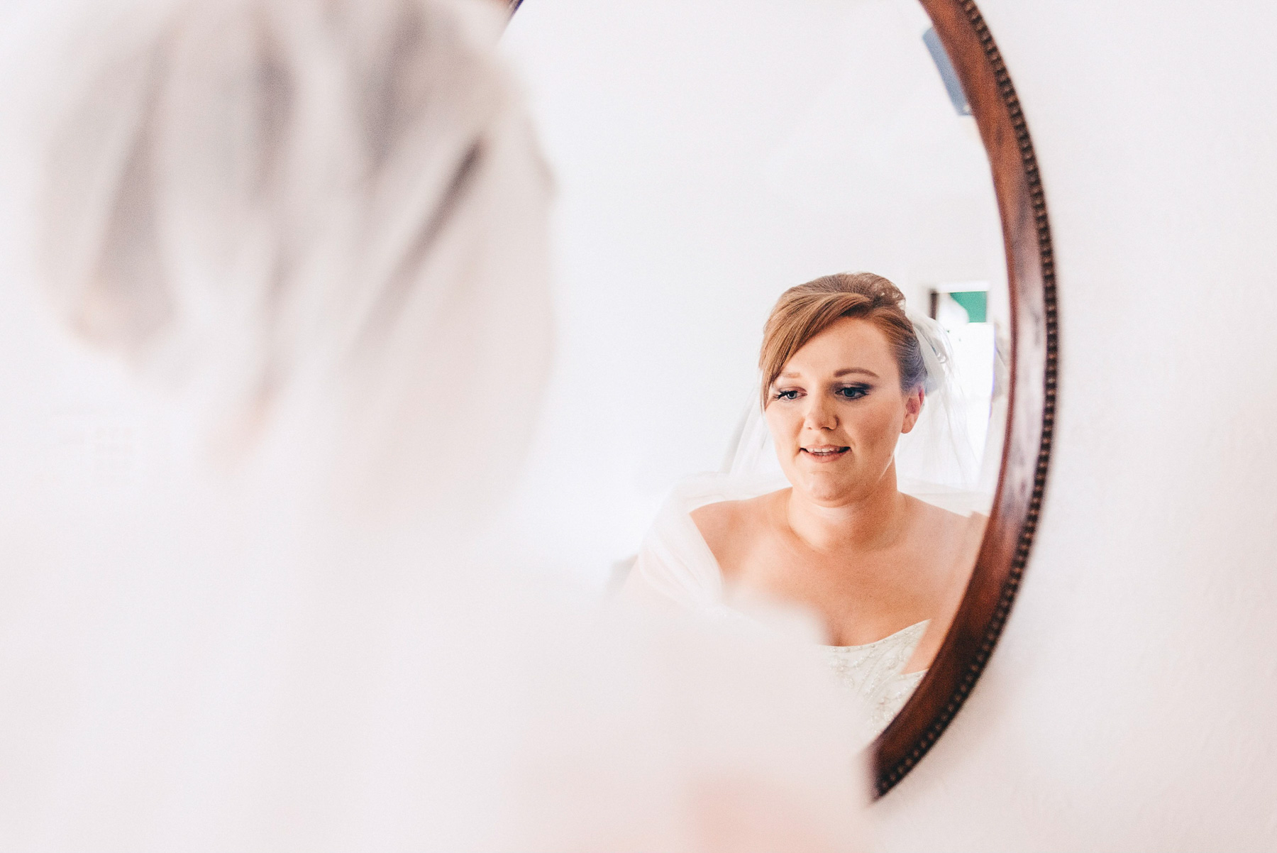 Bride looks in the mirror