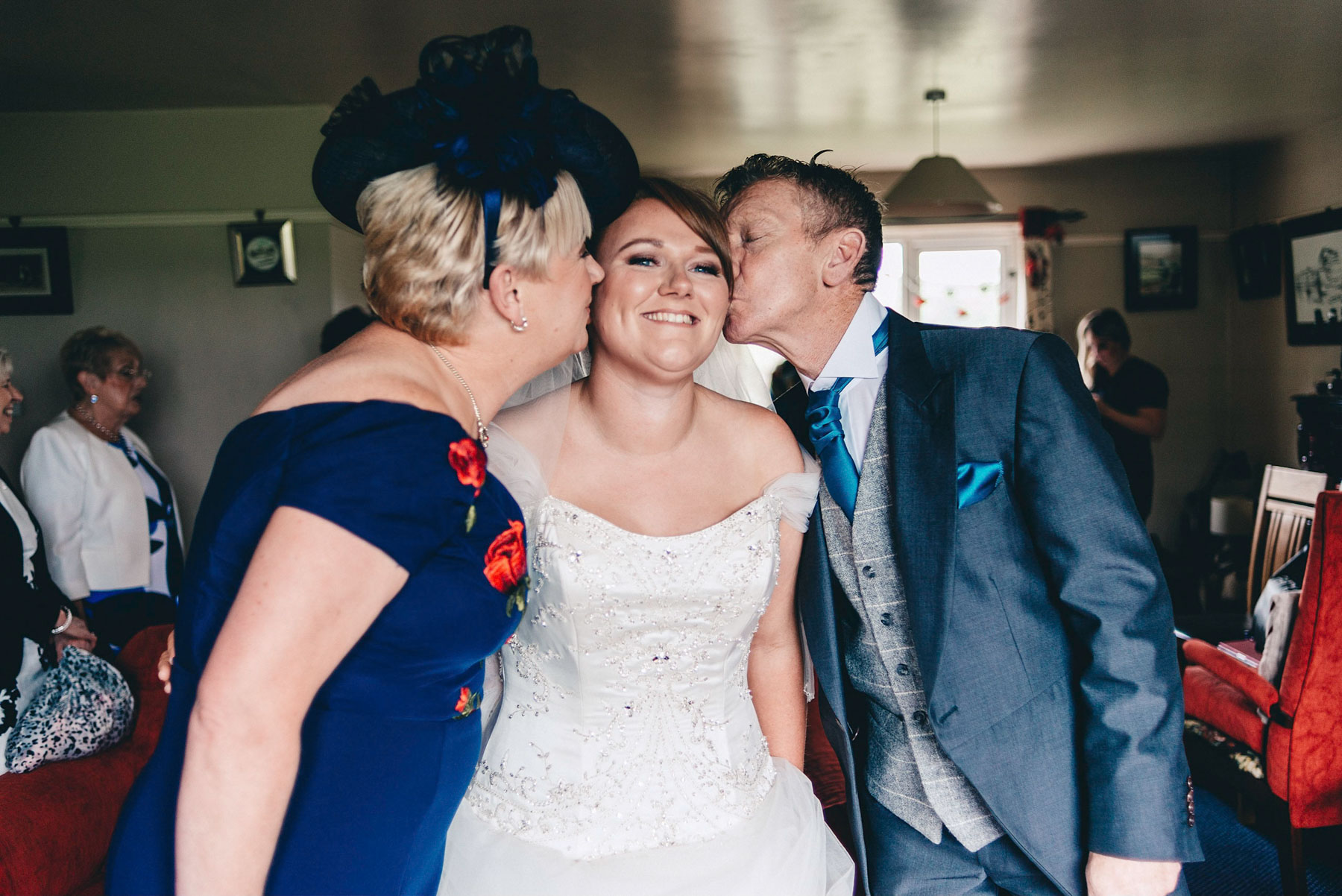 Bride gets kiss from mother and father