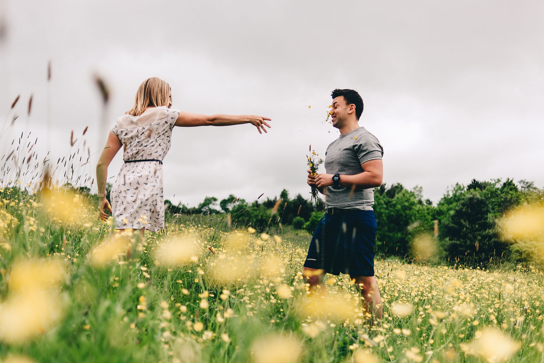 Engaged Couple throw flowers at each other in Holmebrook Valley Park