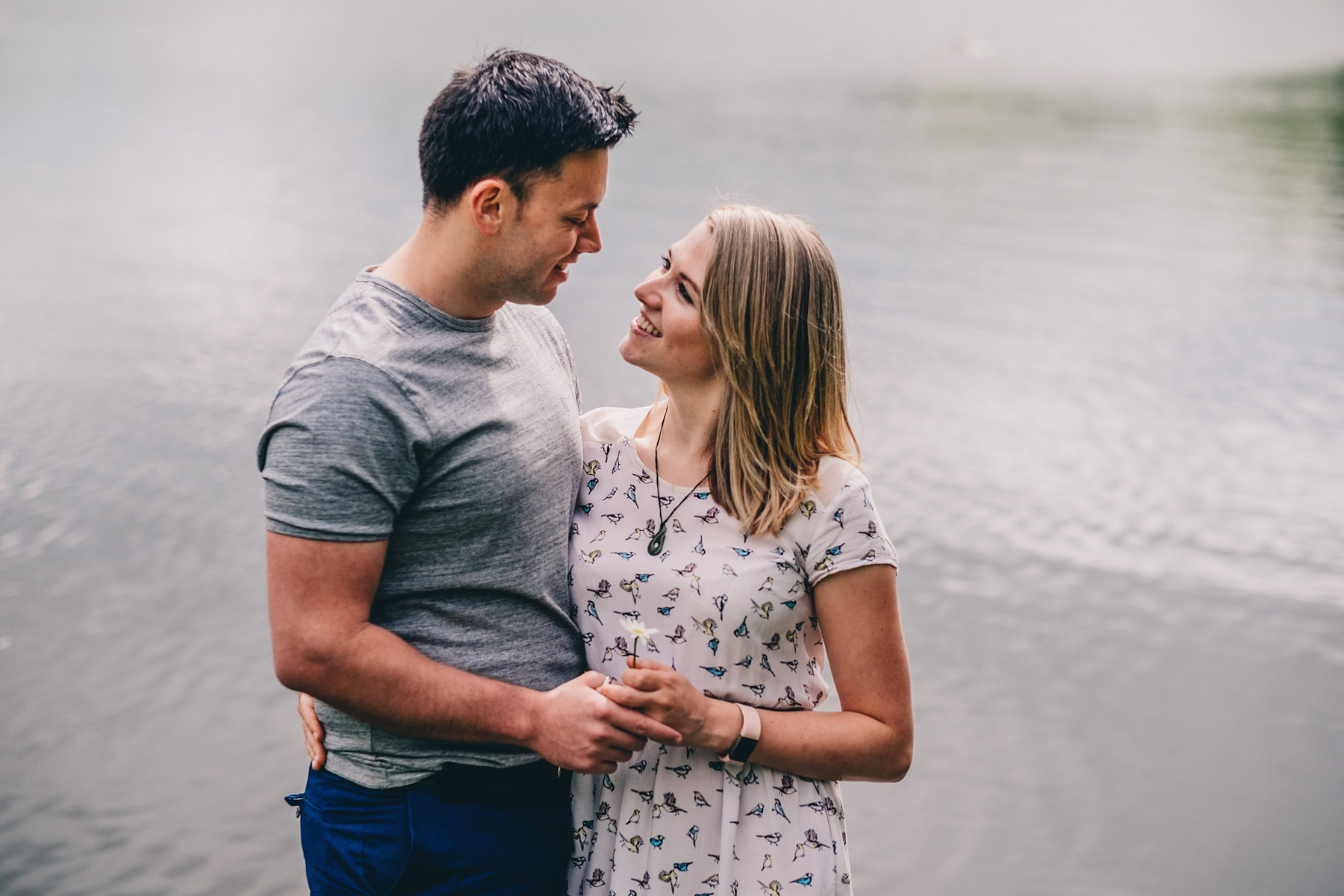 Engaged couple pose in front of lake during engagement shoot in Holmebrook Valley Country Park
