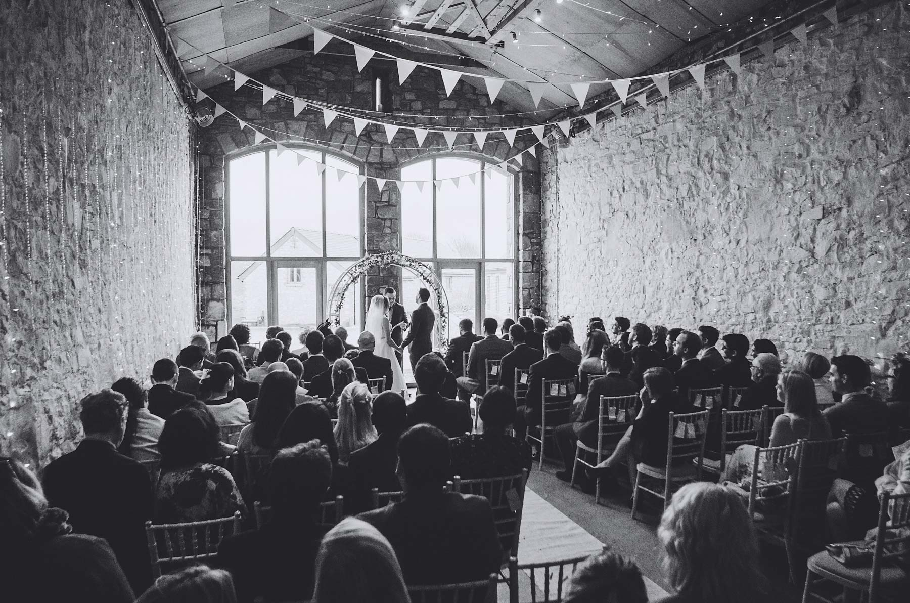 Bride and groom are watched by guests during wedding at Rosedew Farm Llantwit Major South Wales