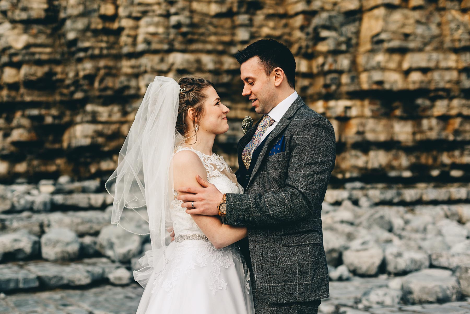 Couple just married stare lovingly by cliffs at Llantwit Major, South Wales