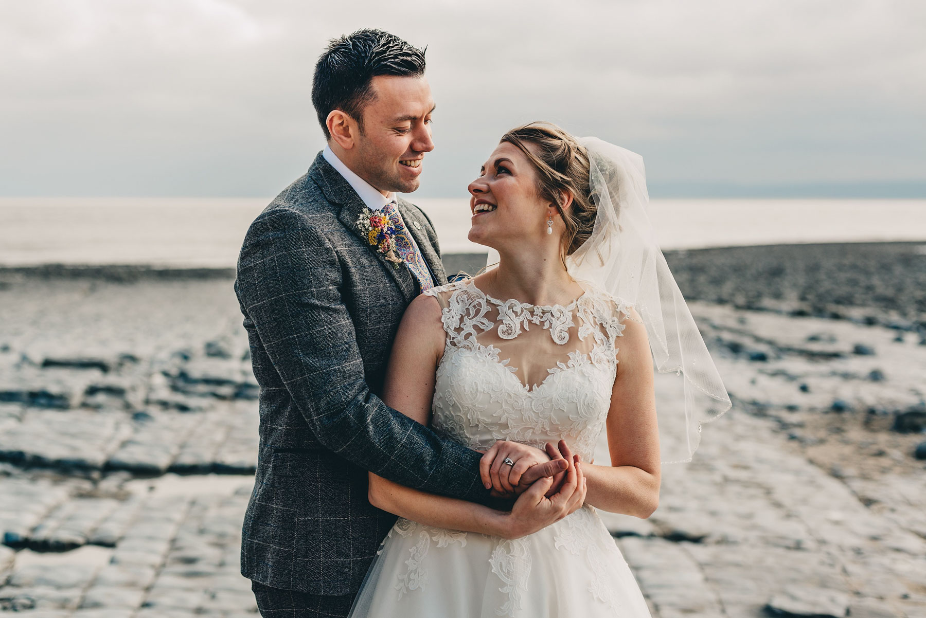 Couple just married hug by coast at Llantwit Major, South Wales