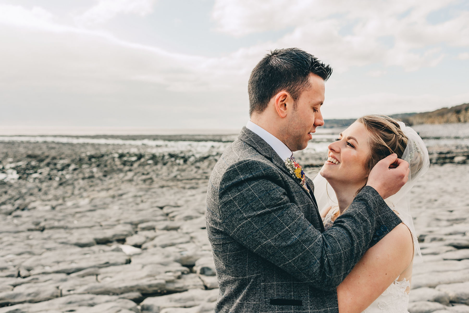 Couple just married stare lovingly at each other by the coast at Llantwit Major, South Wales