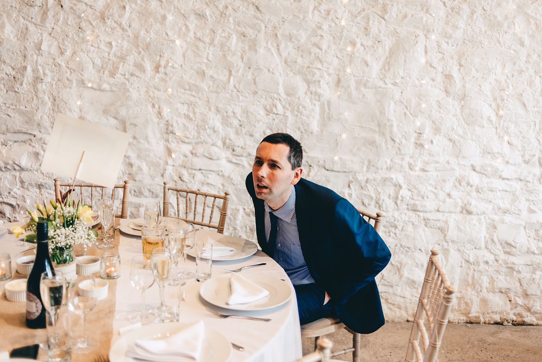 Man stares at table decorations at wedding
