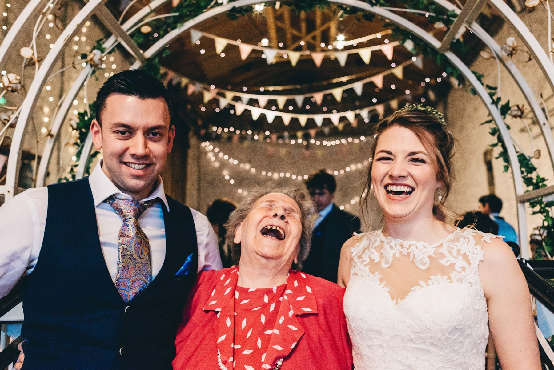 Grandma laughs with Bride and Groom