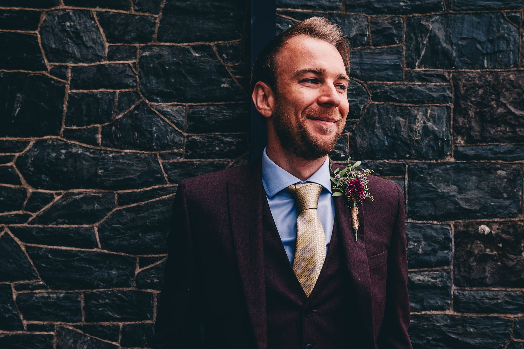Groomsman poses for photo against dark brick