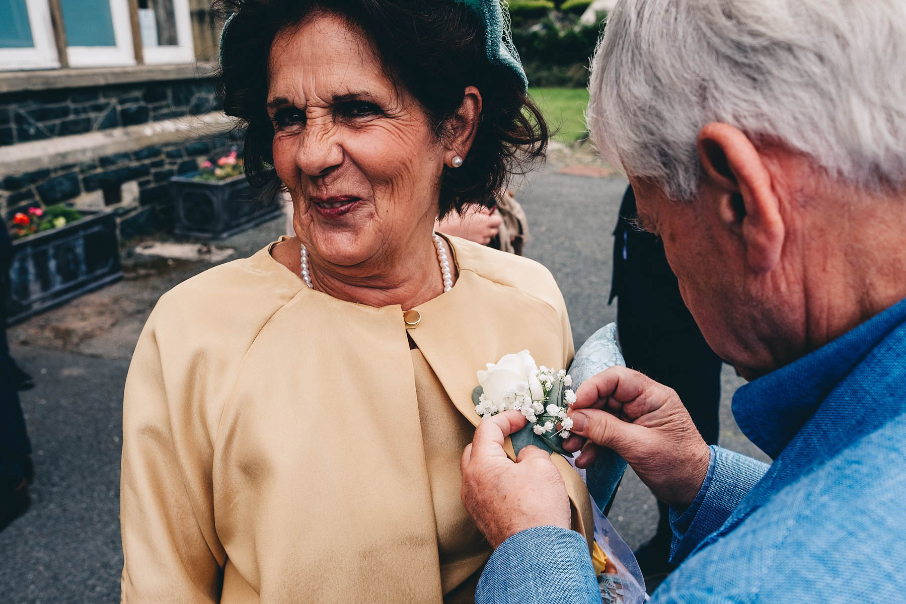 Wedding guest smiles when friend adjusts buttonhole