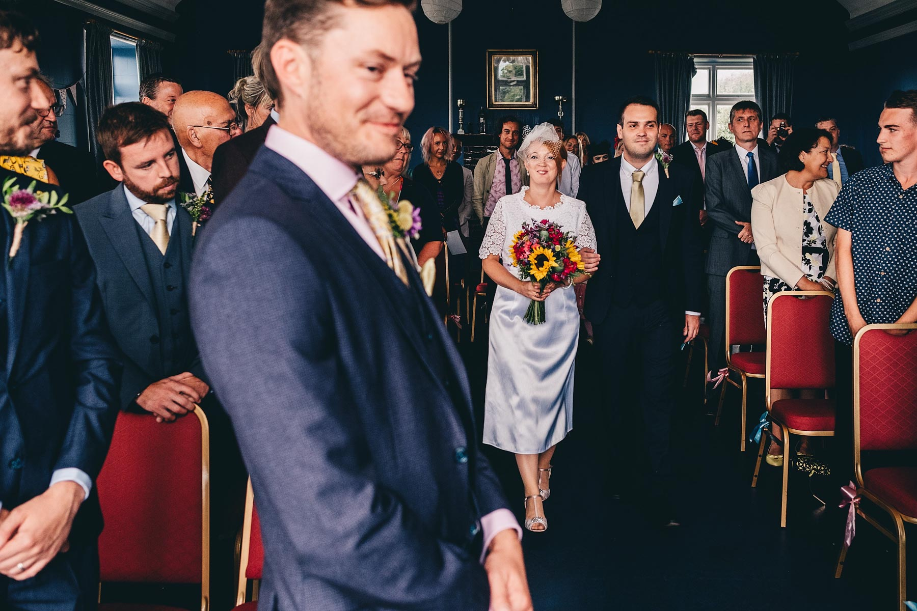 Groom smiles while bride walks up the aisle