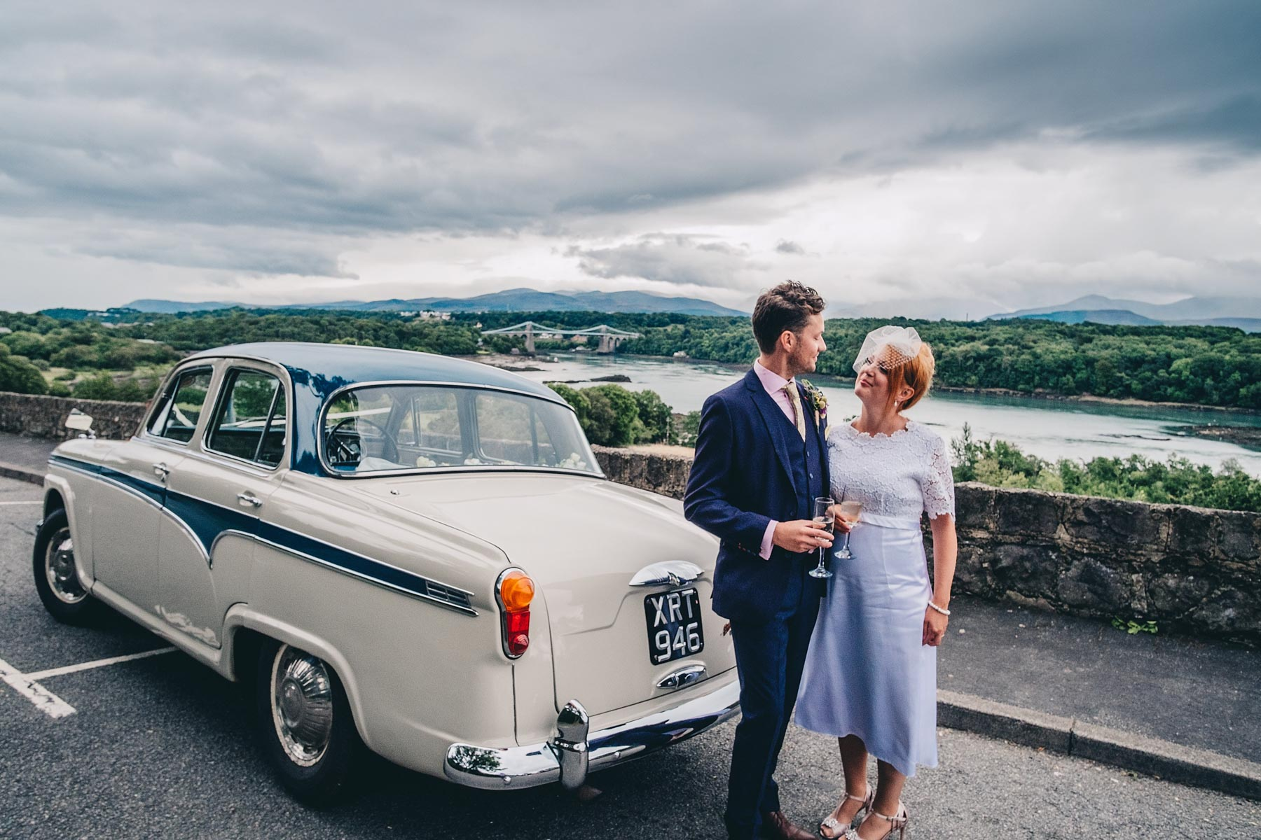 Bride and groom pose next to 1950's car next to The Menai Bridge Viewpoint in North Wales