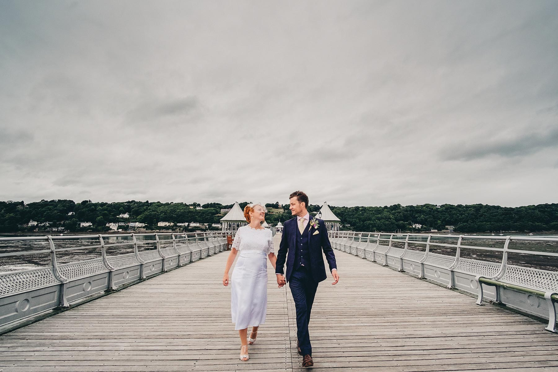 Bride and groom walk down the Bangor Garth Pier looking at each other