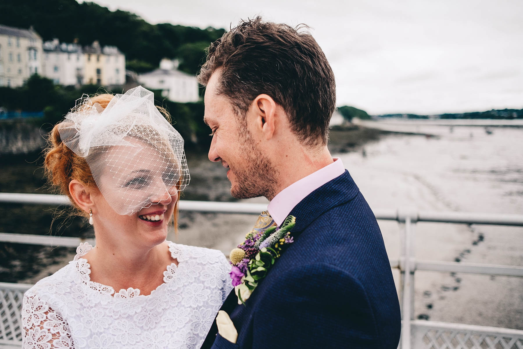 Bride and groom laugh while posing for photos in Bangor Pier