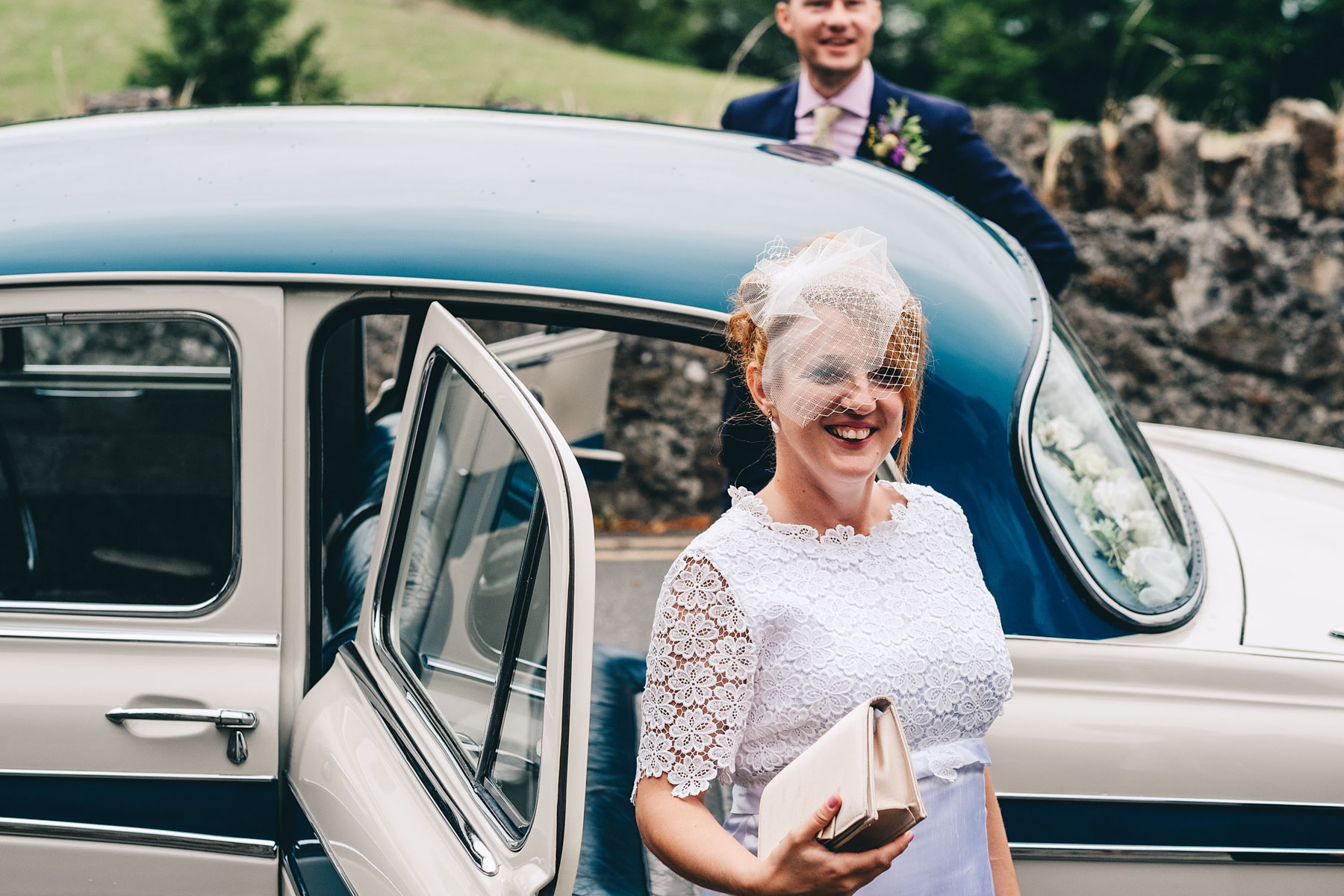 Bride steps out of wedding car and smiles