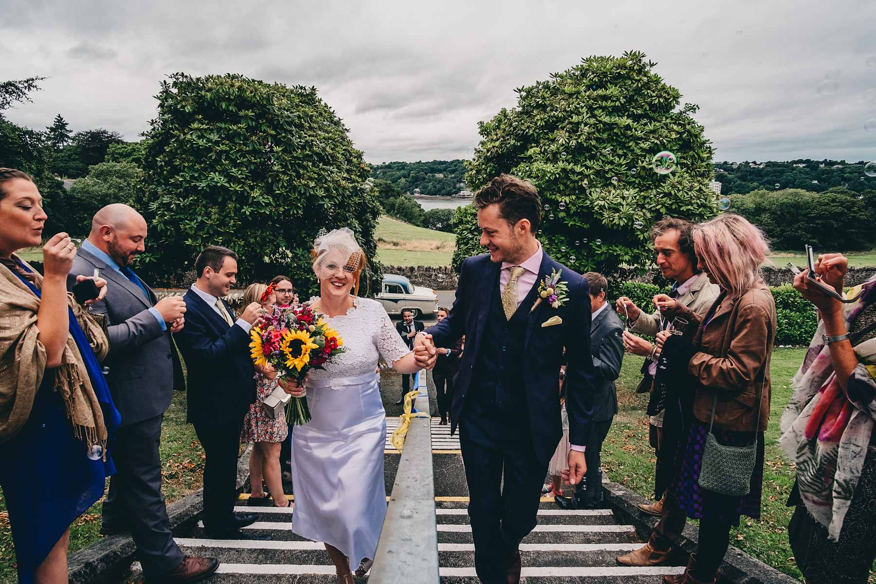 Bride and groom walk up steps of Bangor University