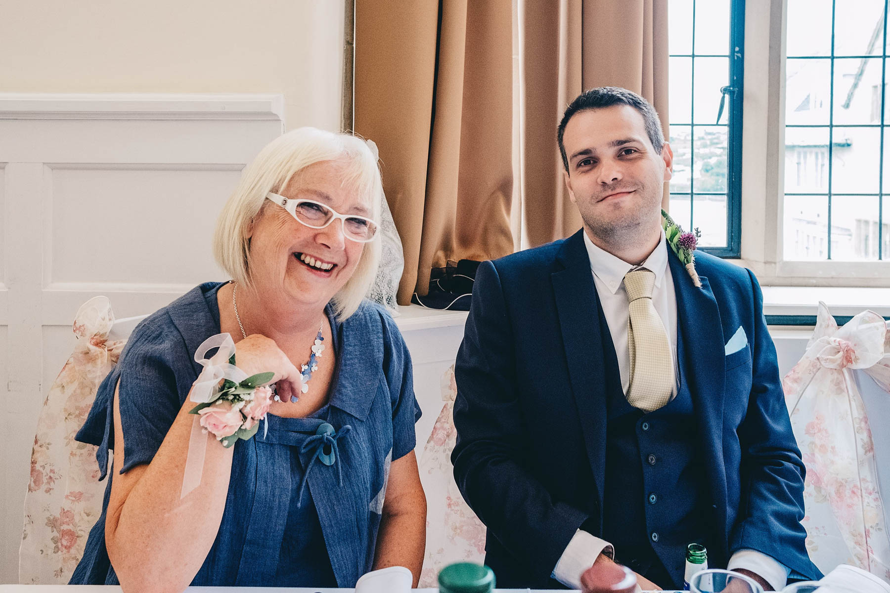 Brother of the Bride smiles with relative during wedding