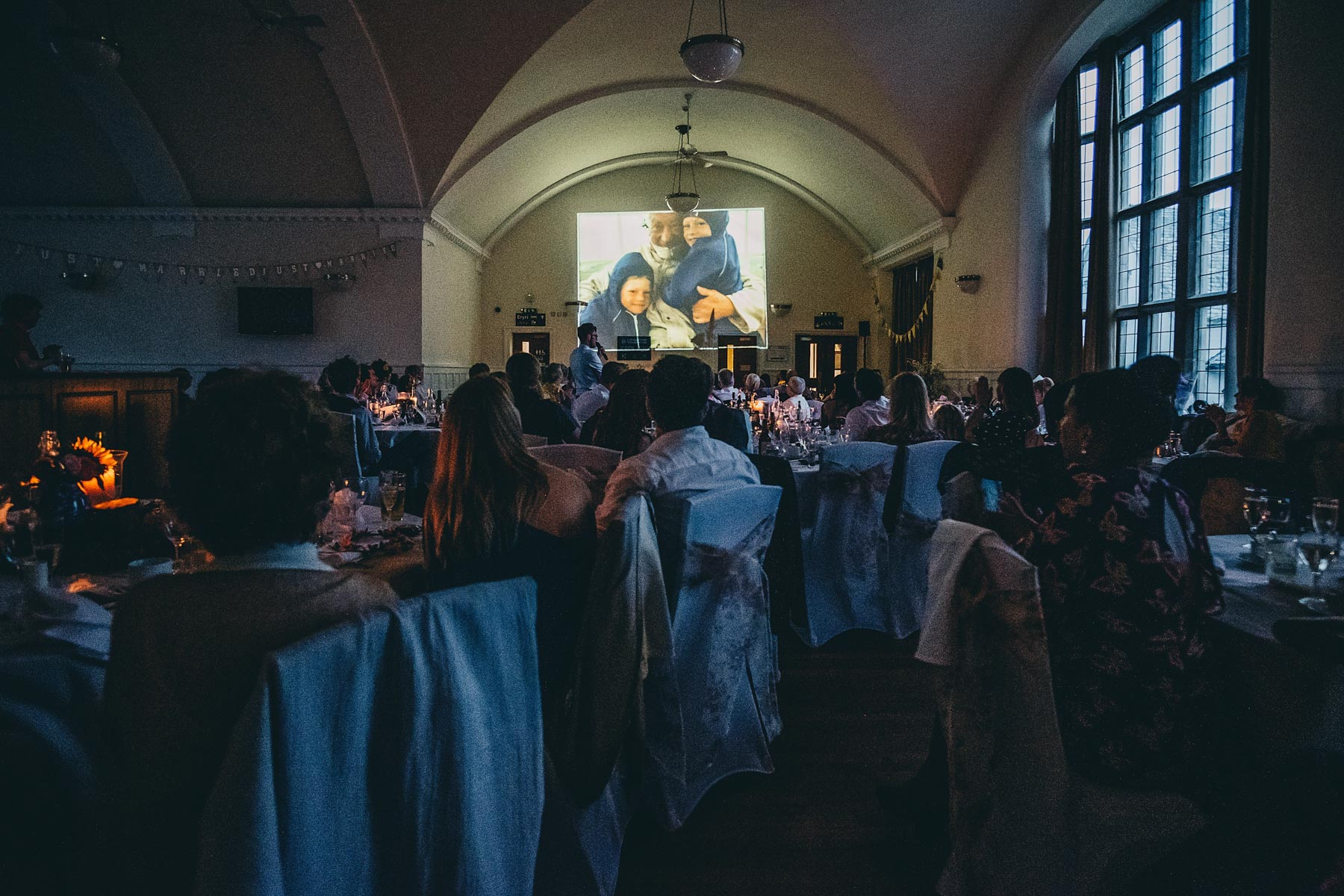 Guests look on during projection at wedding speeches