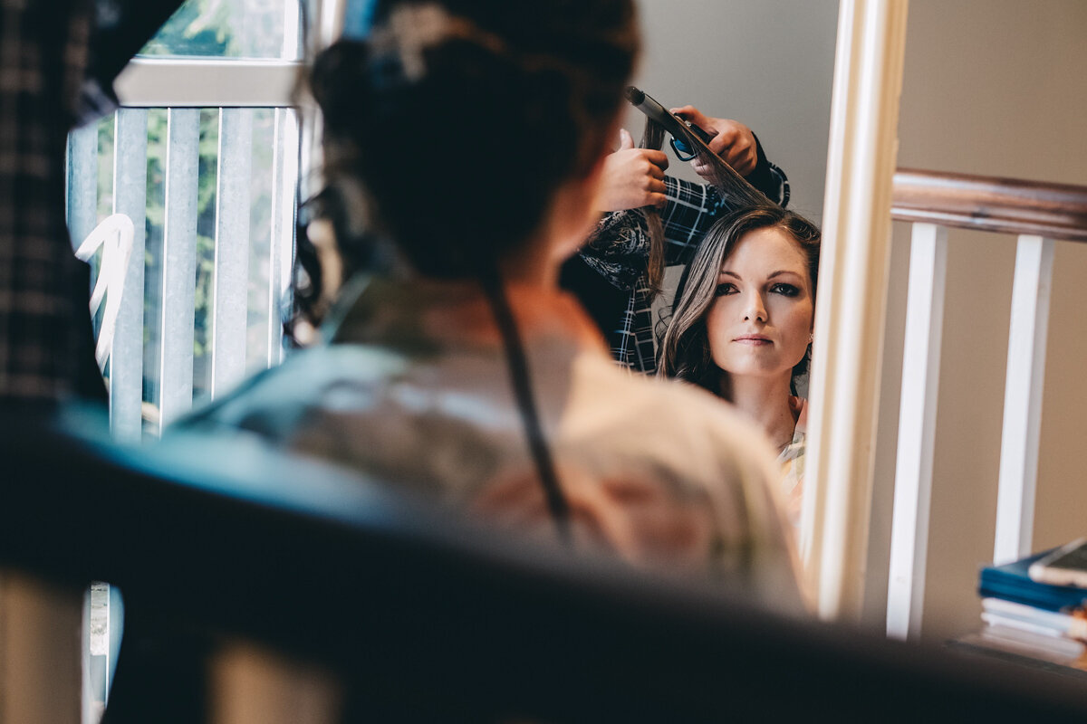 Bride has her hair styled in the morning of her wedding