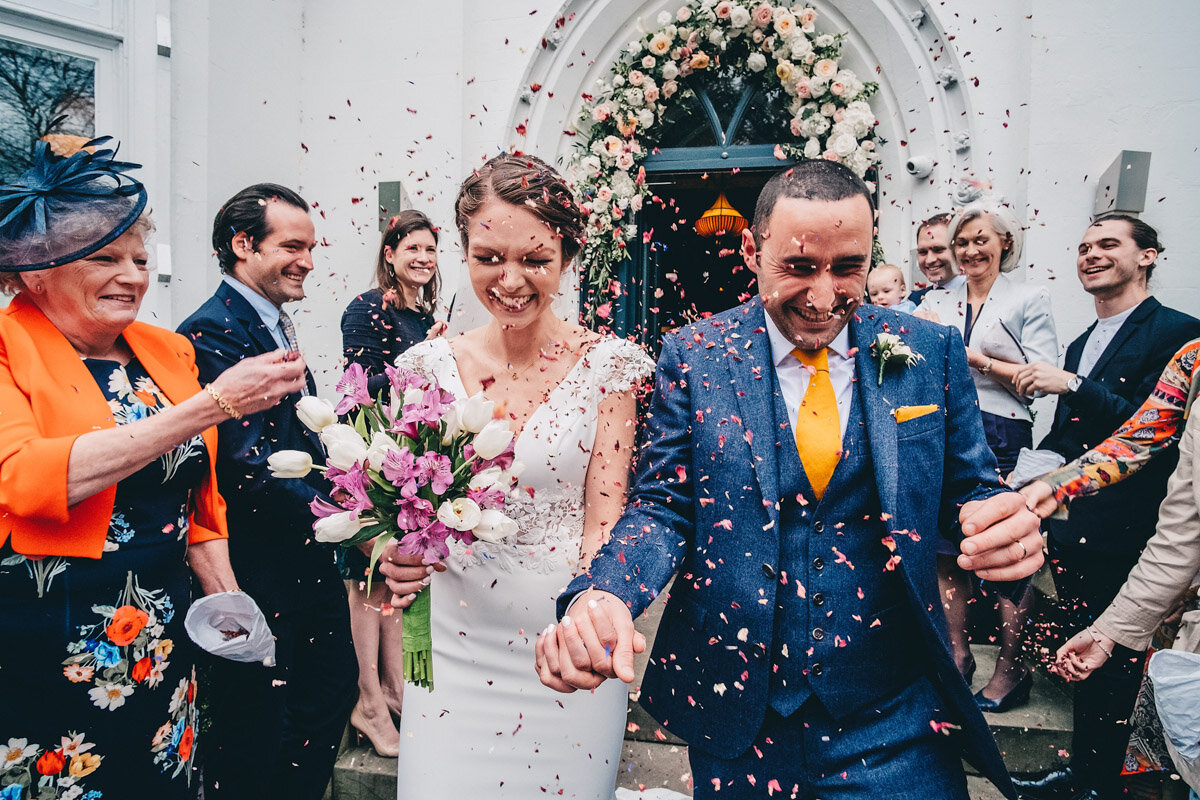 Bride and groom have confetti thrown at them