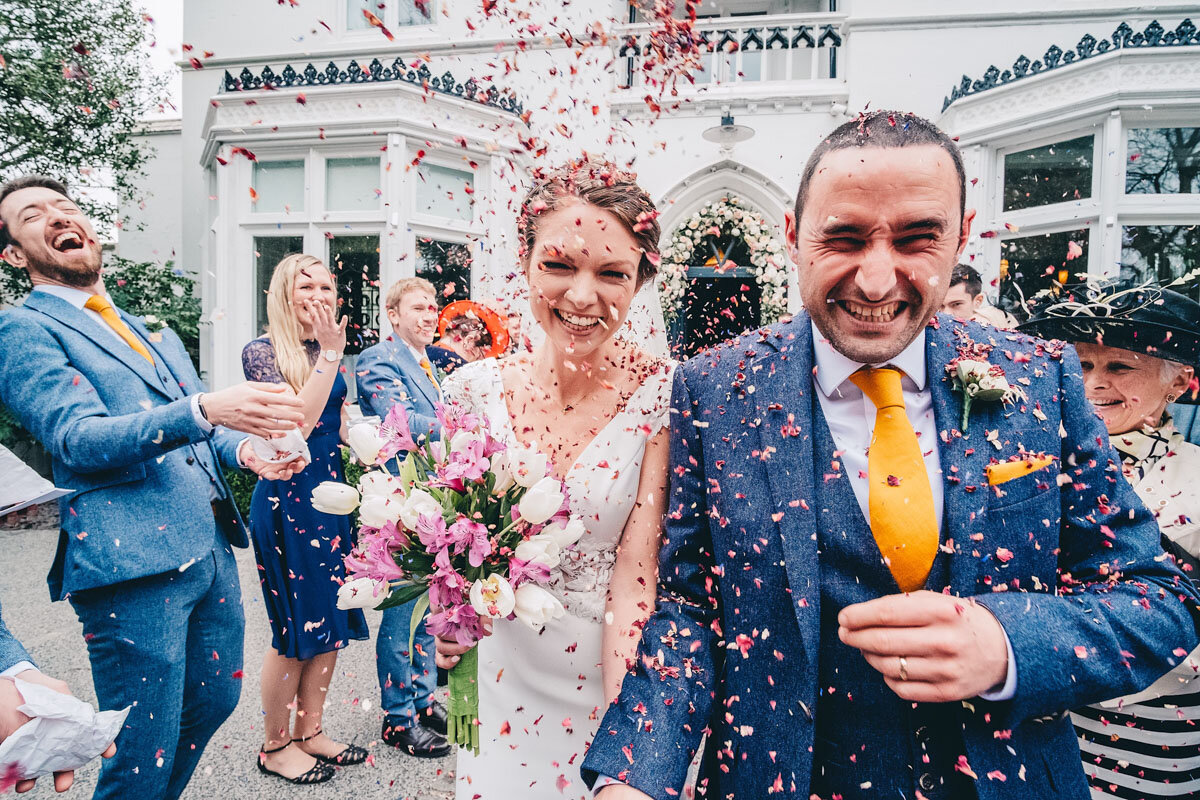 Bride and groom have lots of confetti thrown at them outside the Didsbury House Hotel