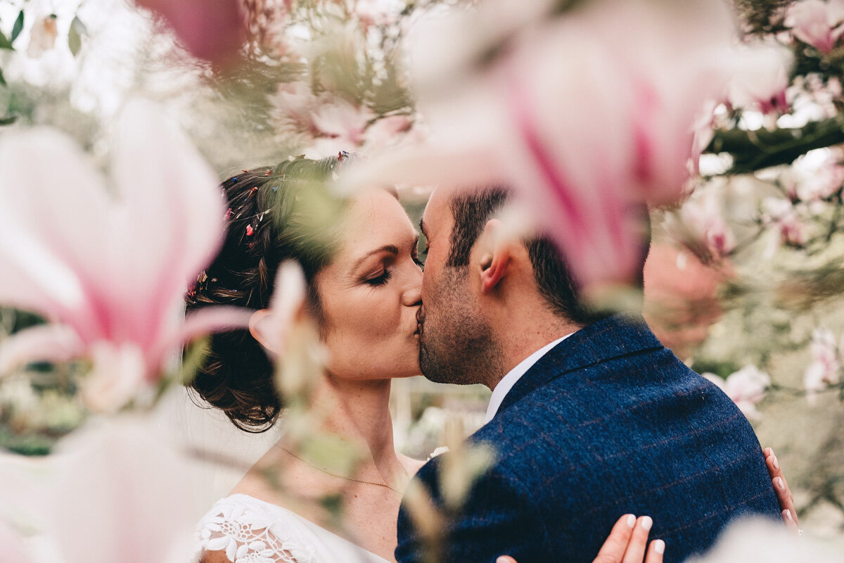 Bride and groom kiss in Didsbury Parsonage Gardens with flowers in full bloom