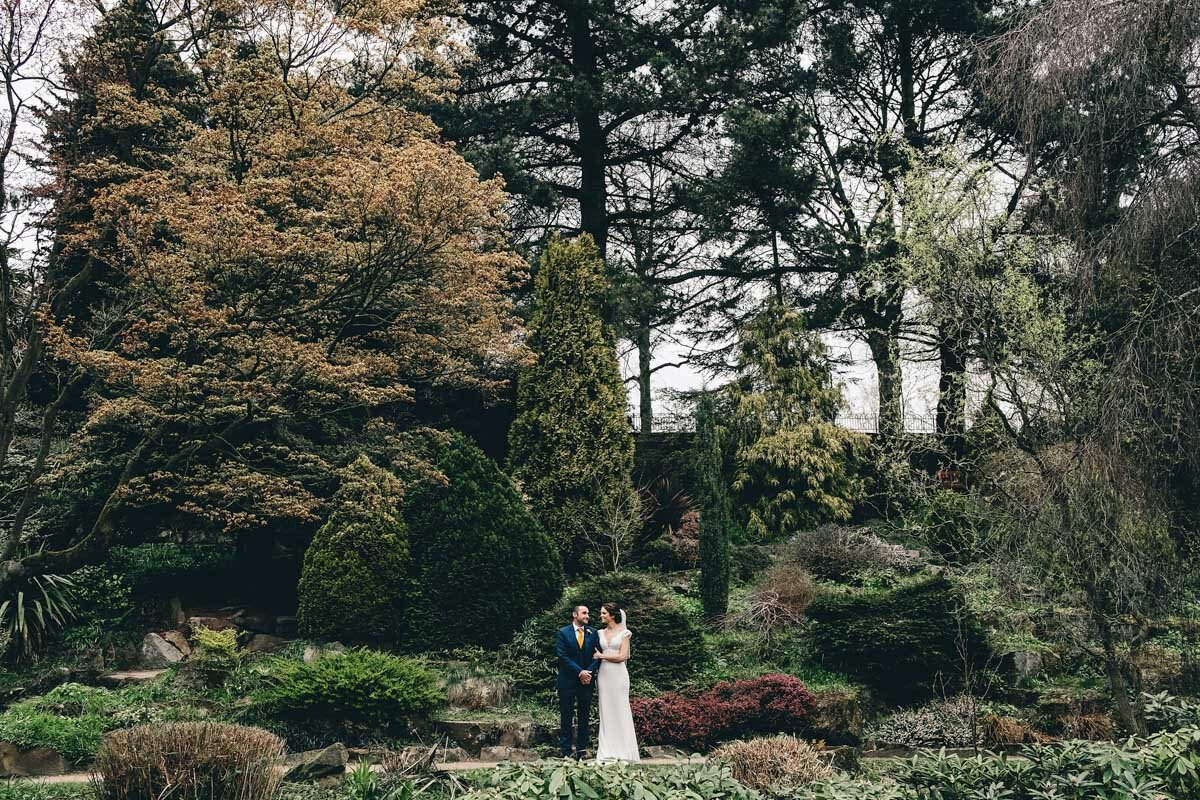 Dramatic shot of bride and groom in Fletcher Moss Park Didsbury