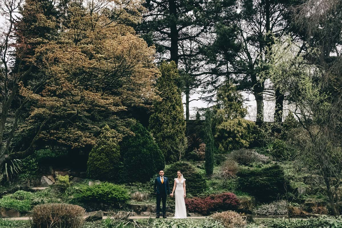 bride and groom pose in the gardens of Fletcher Moss Park Didsbury