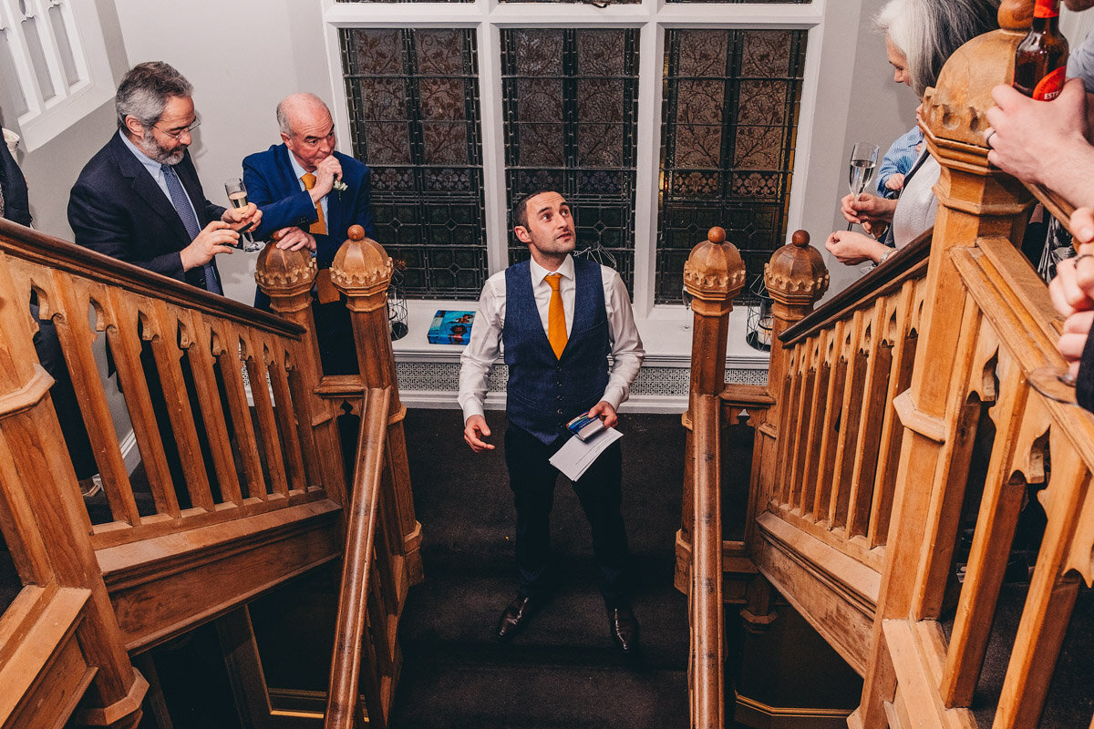 Groom gives his speech at his wedding on the staircase