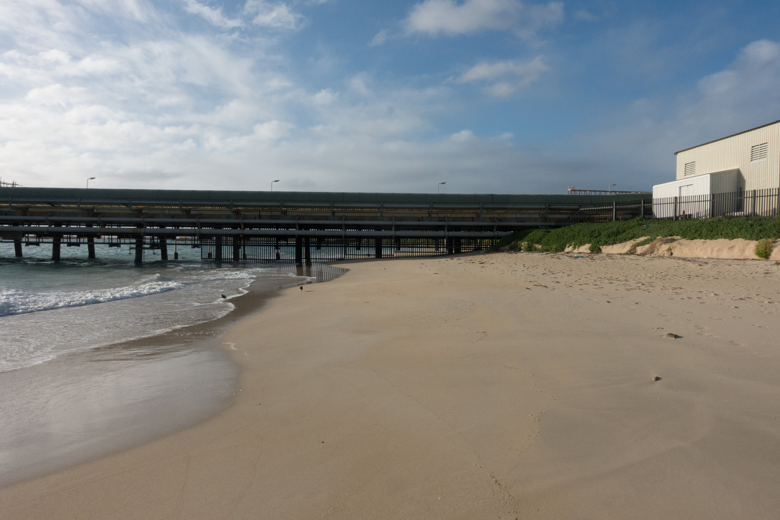Plate 28: Close up of the jetty at the northern end of Kwinana Beach showing the gates underneath the jetty blocking further access and the property fence prevent access around it.