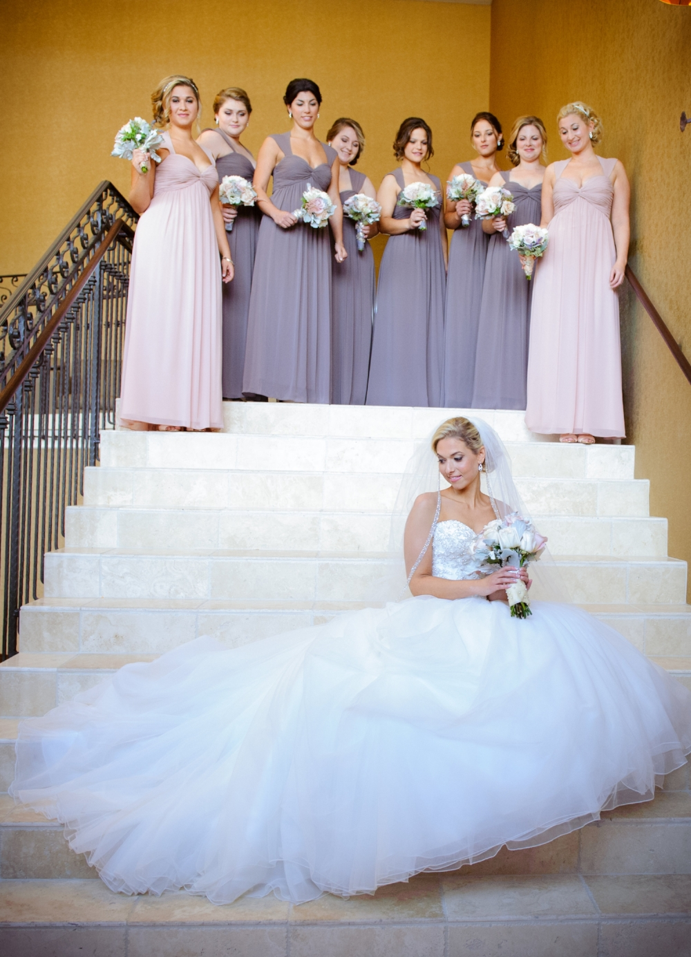 bride-sitting-at-end-of-staircase-bridesmaids-in-background