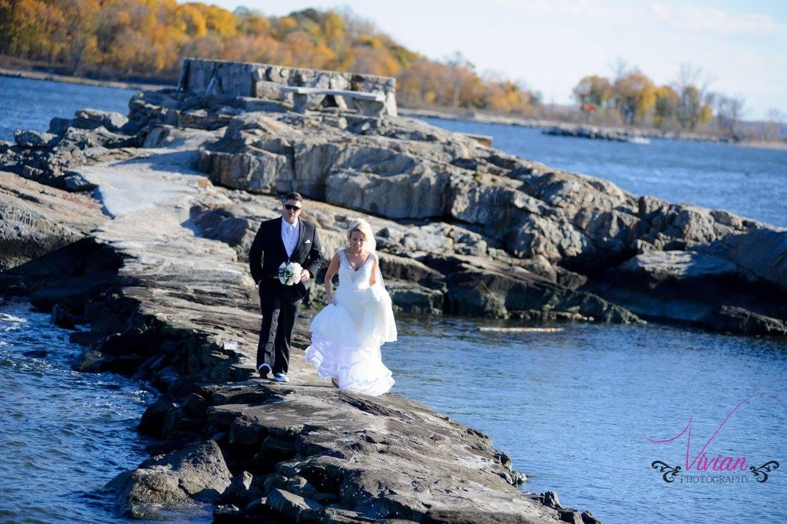bride-and-groom-far-away-walking-towards-camera-on-rocks-over-body-of-water.jpg