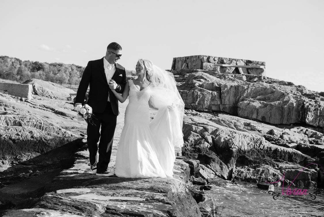 bride-and-groom-walking-through-rocks-near-ocean.jpg