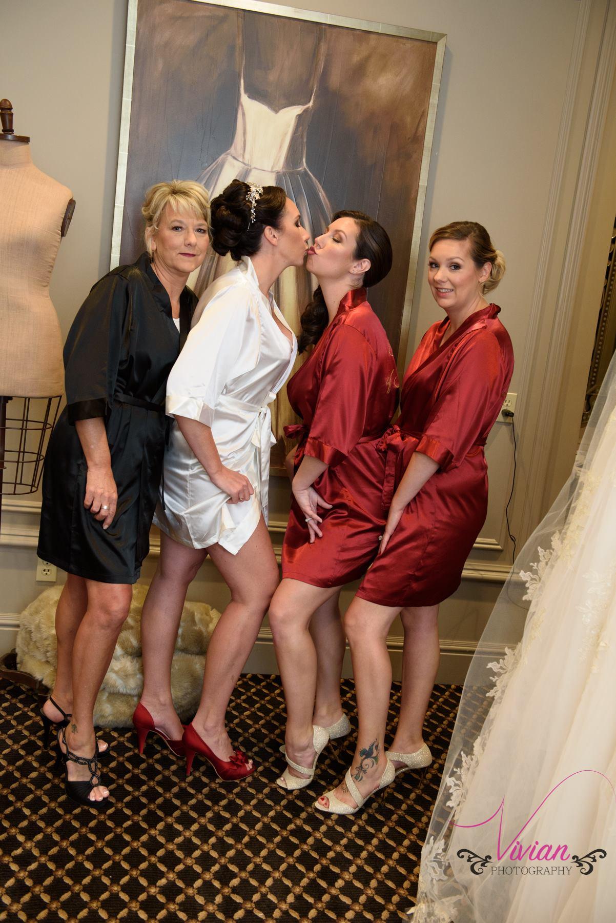 bride-bridesmaids-posing-for-camera-in-satin-robes.jpg
