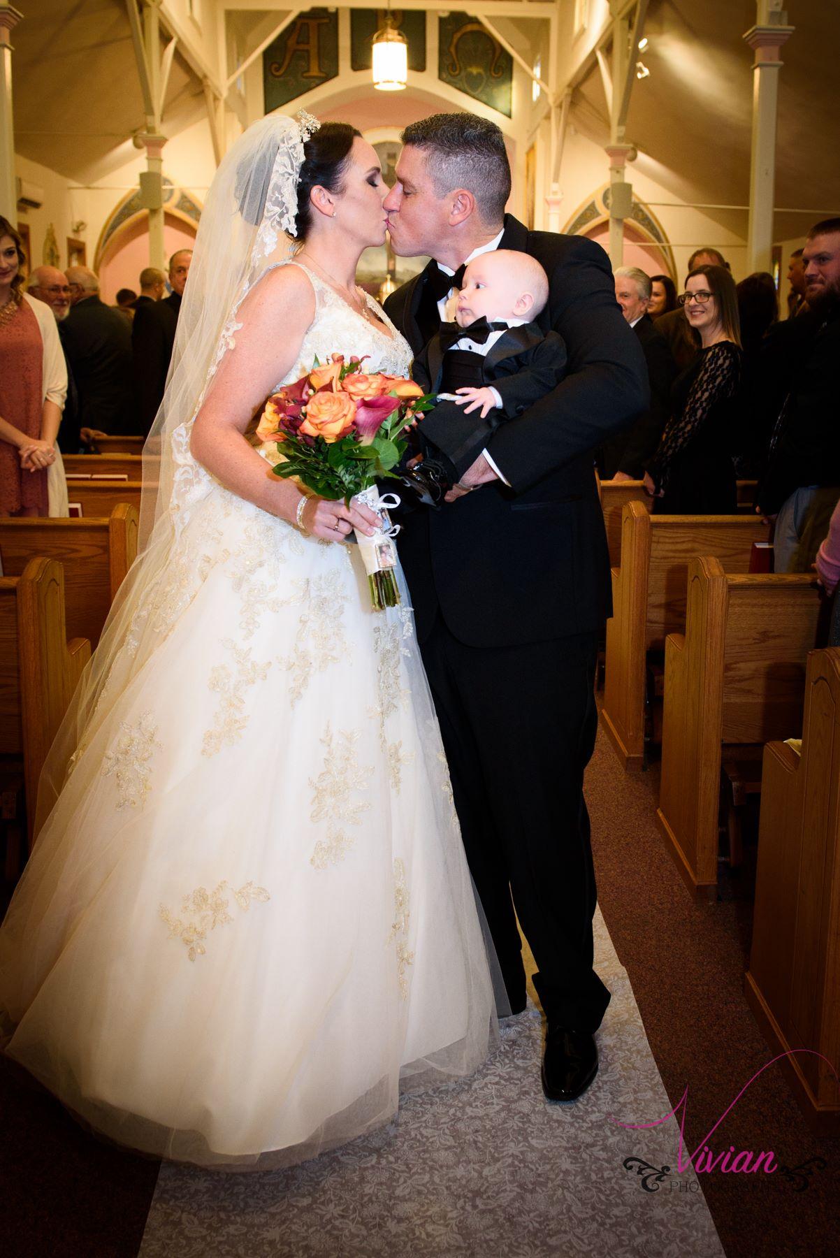 bride-groom-kissing-groom-holding-baby.jpg