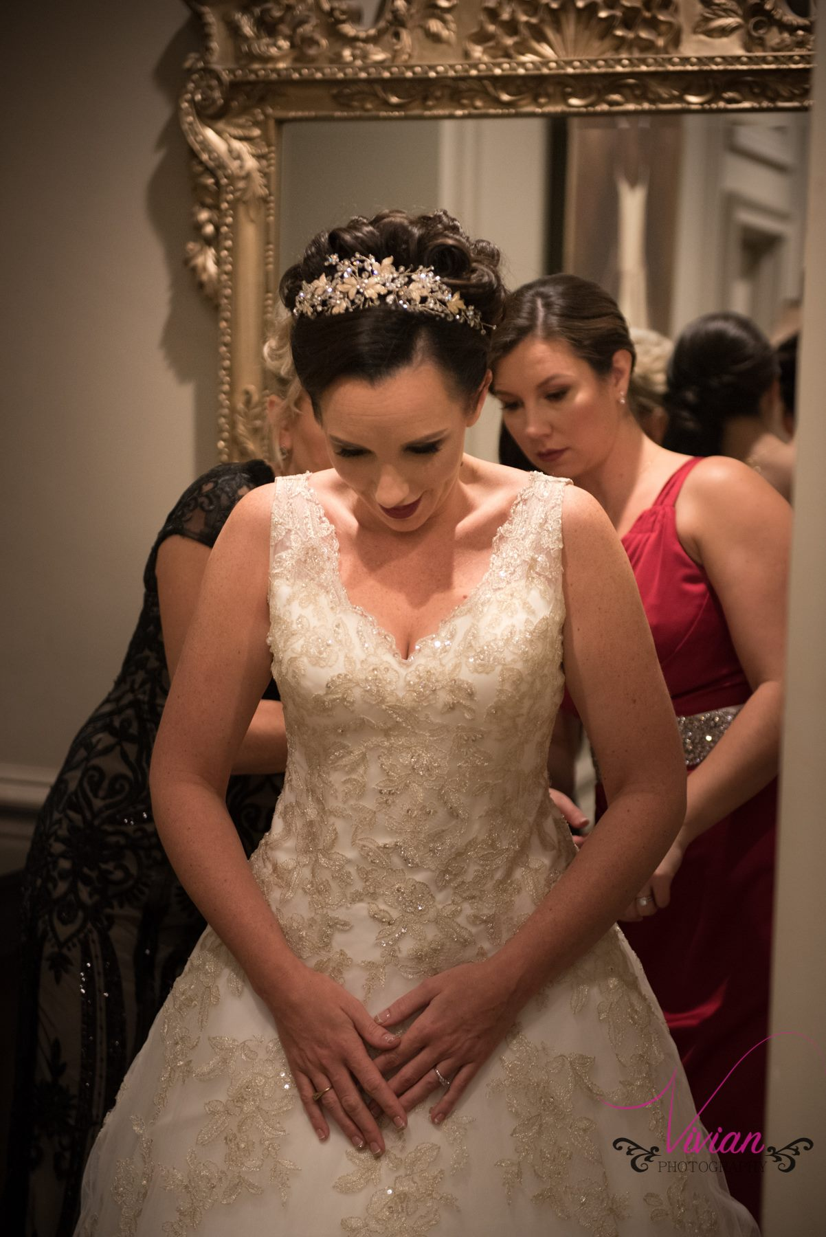 bride-lookin-down-dress-getting-zipped.jpg