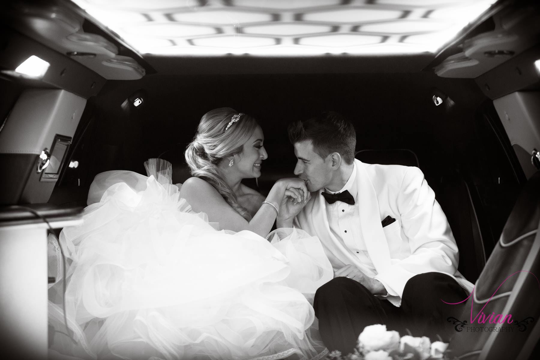 groom-kissing-brides-hand-limo.jpg